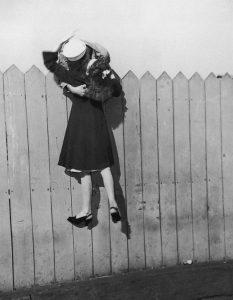 Un soldato si sporge da una staccionata e solleva la sua fidanzata per baciarla (1945) Hulton Archive